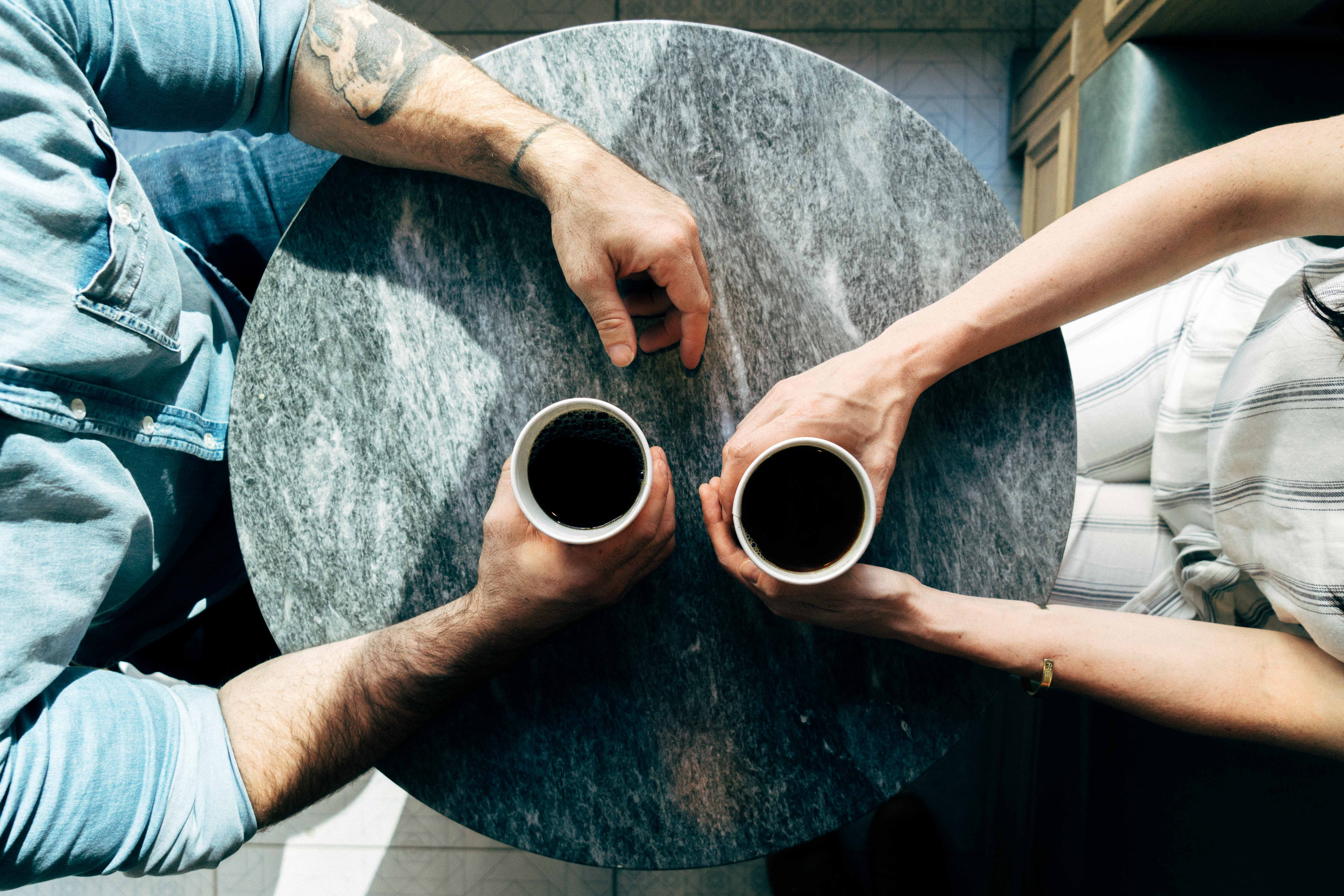 Two people at table with coffee cups to represent informal mentoring