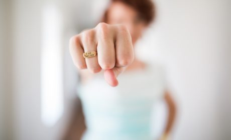 woman with fist out in front showing ring with 'mantra' style statement on it