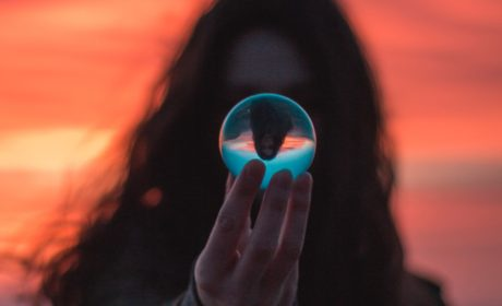 a woman looking into a reflective glass ball to represent looking into the future