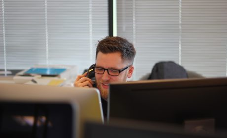 person on phone smiling above computer screen