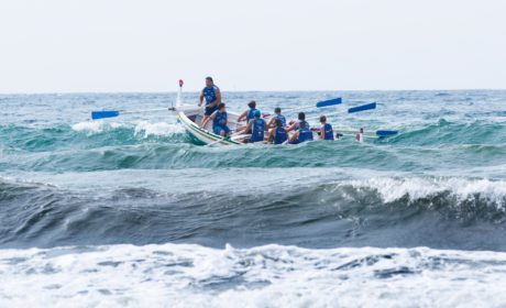 a team rowing a boat in the see with a leader directing.