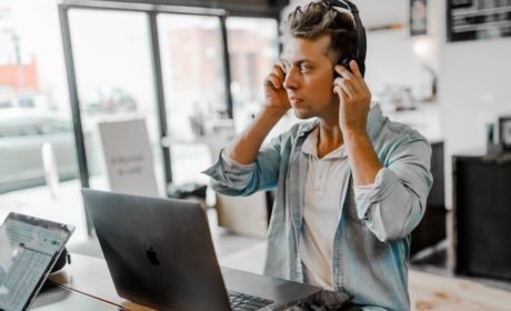 person with headphones in front of laptop