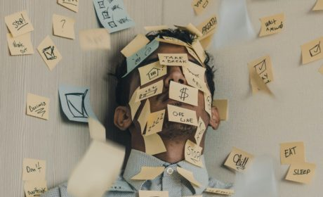 man covered in post-its to show information overload