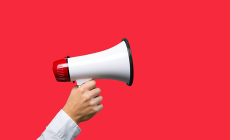 hand with megaphone on a red background